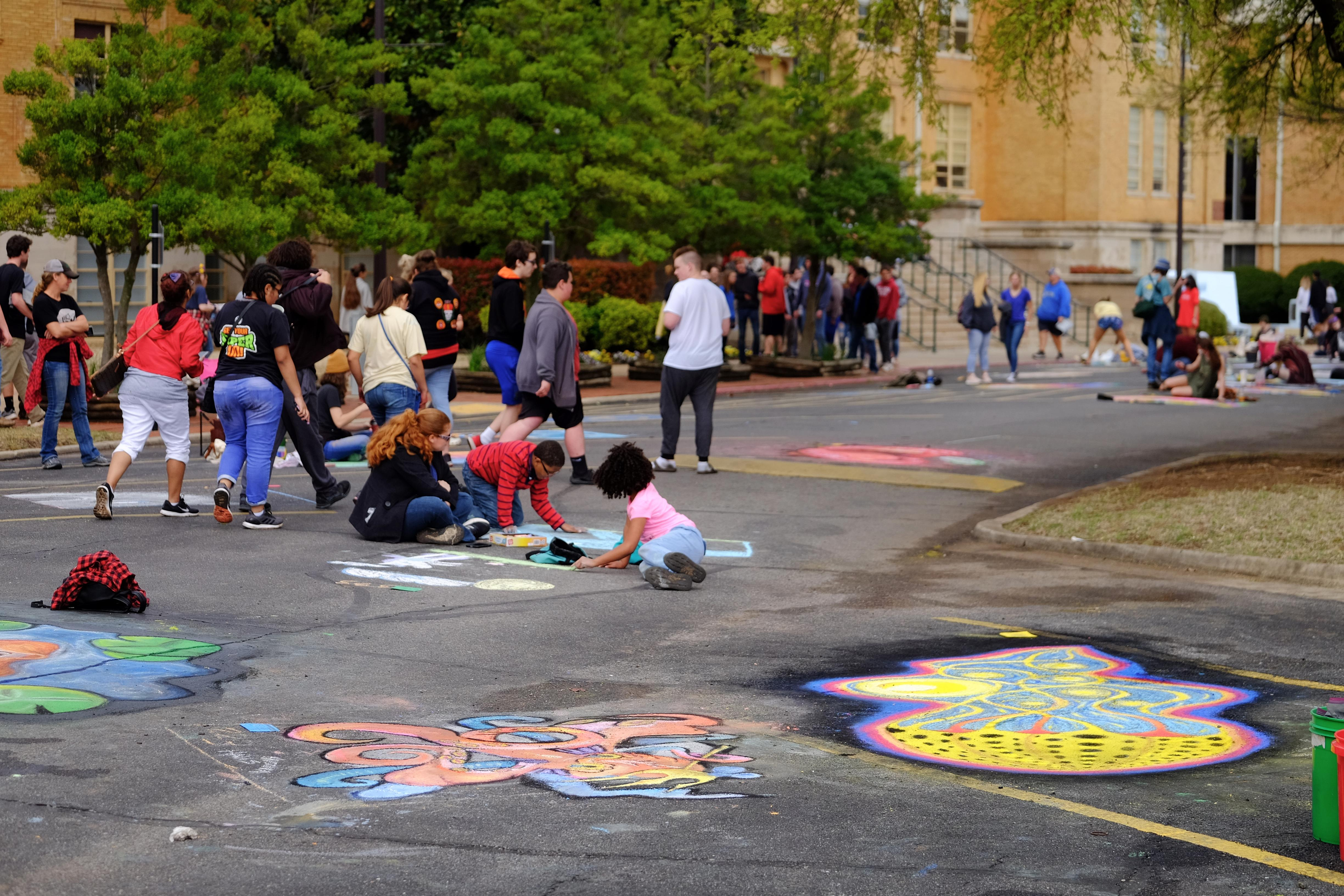 Crowd of people walking by and drawing with chalk