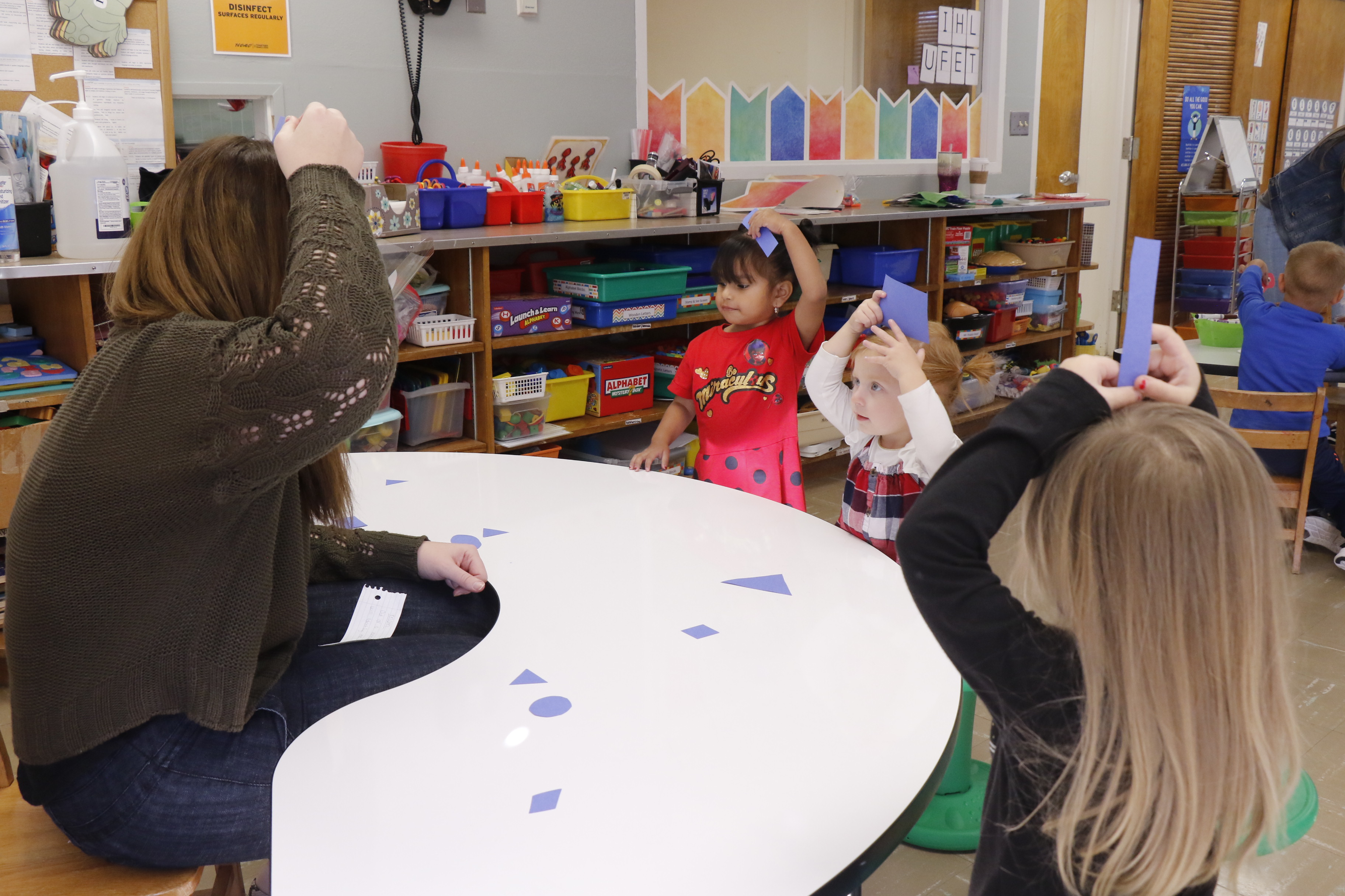 Children playing a shapes game in USAO's Child Development Center