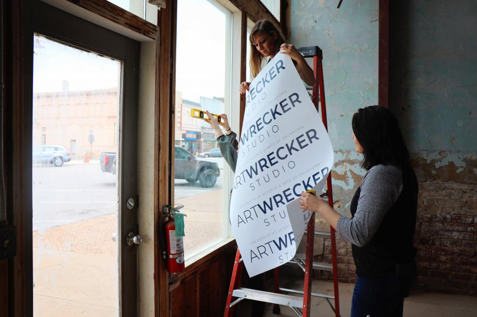 "two women hanging banner with ""Art Wrecker"" on it"